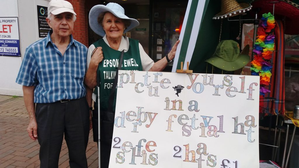 Photograph of EETN Chairman Judy Sarssam holding a poster, with her husband Amer