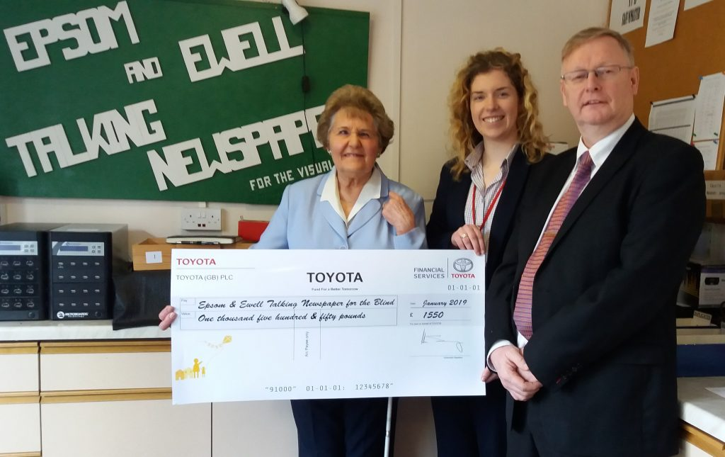 Picture of Judy and Toyota representatives with a very large cheque