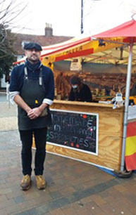 Photograph of Sebastian in front of Taste of Spain market stall in Epsom